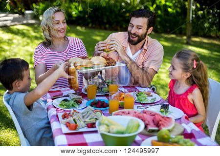 Cheerful family enjoying meal at table in yard