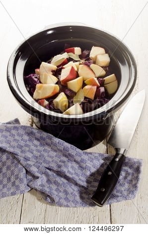 red cabbage with apple and bay leaf in a black slow cooker pot