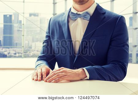 people, fashion, style and wedding concept - close up of best man or groom in suit and bow-tie at table over city office room background