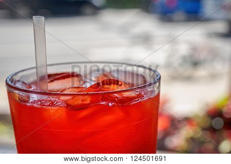 Red cordial drink in a cup, with ice and straw.