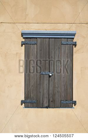 Brown wooden vintage greek shutter on closed and locked window with iron padlock on light orange wall of house building