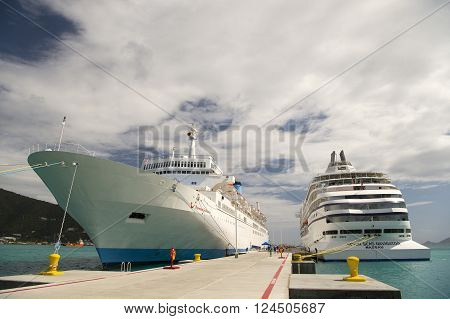 Road Town Tortola - January 26 2016: Large touristic luxury cruise ships standing in bay near deck sunny day with cloudy sky