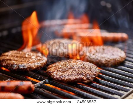 hamburgers and hot dogs cooking on grill with flames