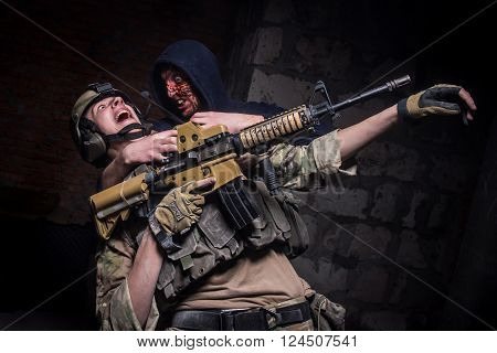 KIEV,UKRAINE - February 20 : KIEV,UKRAINE - February 20 : Mad zombie attacked soldier with gun during thematic game about zombies in Kiev,Ukraine on February 20,2016.
