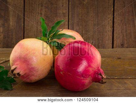 Close up photo of three imperfect whole pomegranates on wood background