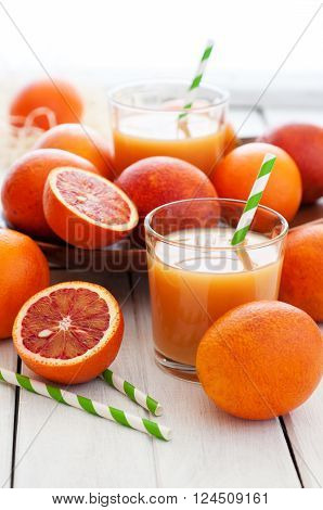 Fresh oranges juice with fruits on white wooden table selective focus vertical