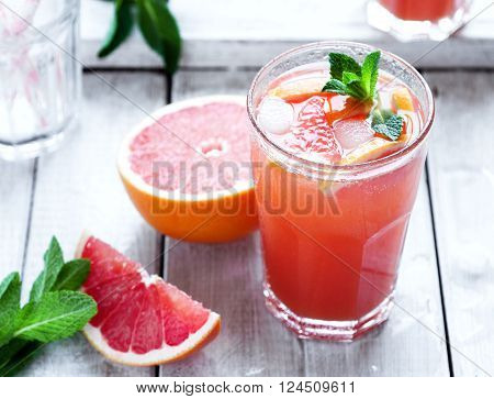 Fresh pink grapefruit juice with mint and crushed ice on wooden background selective focus horizontal