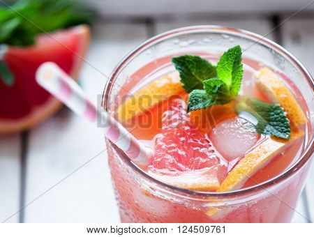 Close up of fresh juice with pink grapefruit and crushed ice on wooden background selective focus