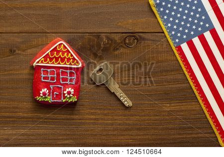 Red sweet house key and american flag on wooden background