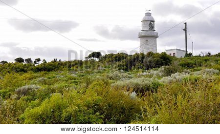 Cape Naturaliste Lighthouse in the green vegetated dunes on the Leeuwin-Naturaliste ridge in Dunsborough, Western Australia under stormy skies.