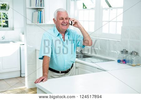 Happy senior man talking on phone in kitchen at home