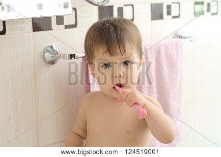 Kid Cleaning Teeth In Bathroom