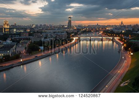 Borodinsky bridge with illumination on Moskva river in evening in Moscow, Russia