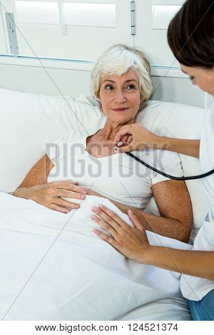 Female doctor auscultating old woman with stethoscope at home
