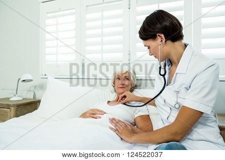 Female doctor auscultating aged woman against window at home
