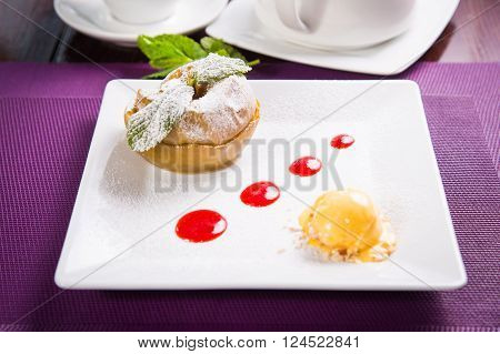 baked apple with fresh mint,sherbet and red sauce in white dish