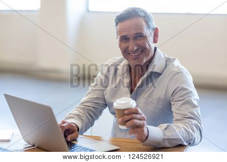 Portrait of businessman holding disposable coffee cup and using laptop at his desk in the office