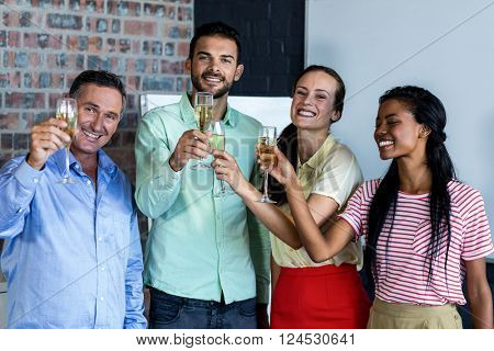 Colleagues toasting champagne flutes in office poster
