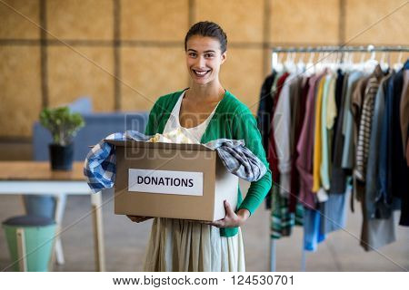 Portrait of young woman with donation box in the office