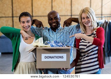 Portrait of colleagues holding and pointing at donation box