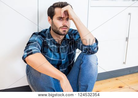 Tensed man with hand on forehead sitting on wooden floor at home