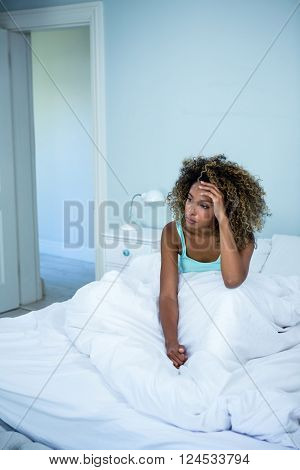 Tensed woman sitting on bed with hand on forehead in bedroom