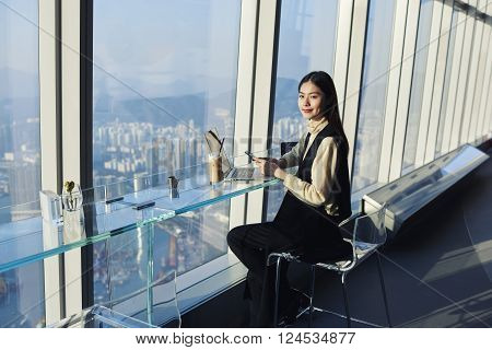 Chinese female CEO is holding mobile phone in hands while is sitting in skyscraper building with Honk Kong city view outside the window. Young successful businesswoman is using laptop computer