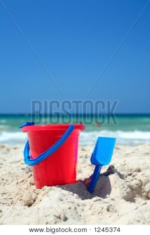 Red Bucket And Blue Spade On Sunny, Sandy Beach