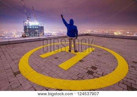 Man stands on helipad on roof of tall building in night with in city