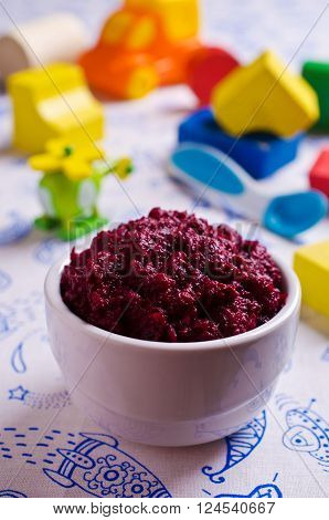 Baby food from beets on the table against the background of toys. Selective focus.