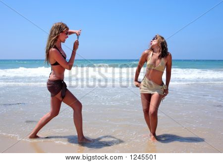 Two Sexy Young Women Playing On The Beach On Vacation Or Holiday