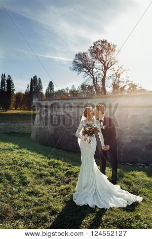 Romantic Newlyweds Holding Hands Near Castle Wall At Sunset