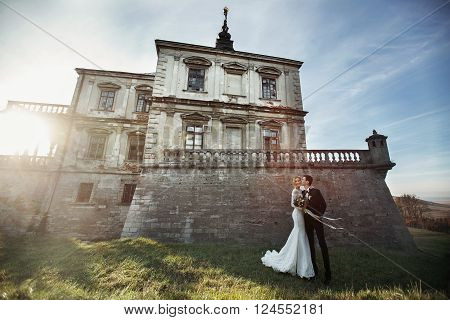 Beautiful Fairytale Newlywed Couple Kissing Near Old Medieval Castle