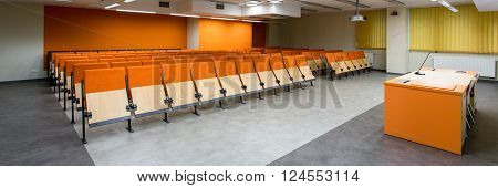 Rows of orange chairs in spacious leture hall with arble floor and new technology