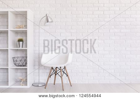 White regale with home decorations, standing lamp and modern chair standing in light room with brick wall design