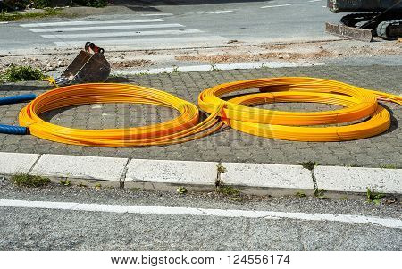 long coils of orange plastic pipes for the installation of underground utilities and energy of optical fibers