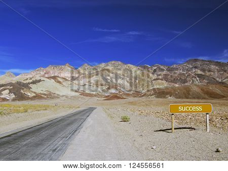 Road to mountains with brown guidepost (success)