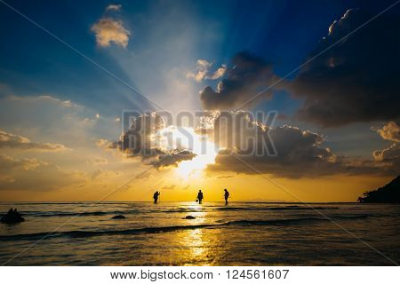 silhouette fishermens at sunset catch sea crabs