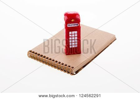 Isolated telephone booth on a spiral note book on white background