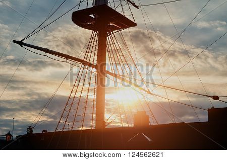 Closeup view of masts and rigging of a sailing ship against the colorful sunset sky. Picturesque travel background