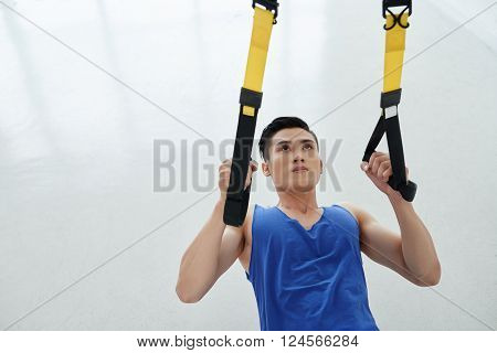 Sportsman using trx fitness straps when performing chin-ups