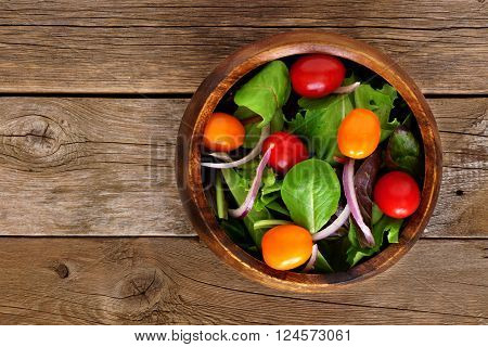 Garden Salad With Cherry Tomatoes And Red Onions In Wooden Bowl Overhead View On Rustic Wood