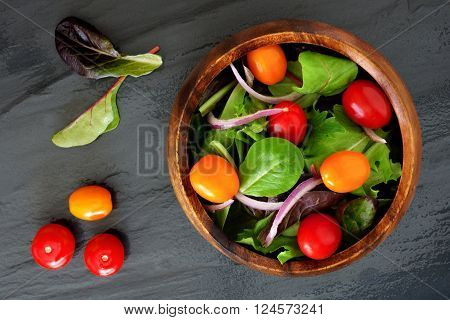 Garden Salad With Cherry Tomatoes And Red Onions In Wooden Bowl, Overhead Scene On Slate Background