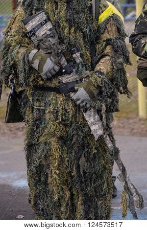 Sniper rifle in hands of sniper in camouflage ghillie suit