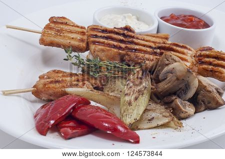 kebab with grilled vegetables and sauce on a white plate closeup