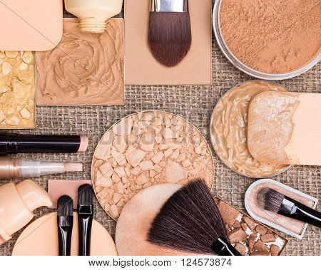 Makeup products to create the perfect complexion. Liquid and cream-to-powder foundation, compact, loose and shimmer golden powder, crushed bronzing powder, brushes and cosmetic sponges on sackcloth
