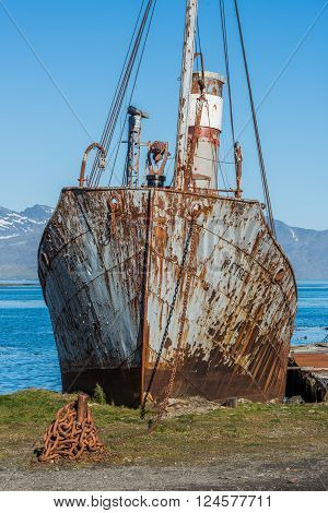 Close-up of old rusting whaler chained up