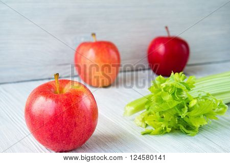 Apples And Bunch Of Celery On A White Table