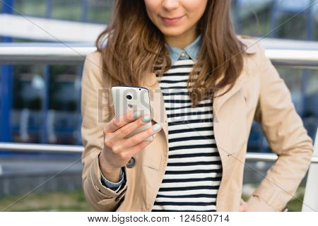 Smiling Girl In A Beige Jacket And A Striped T-shirt Using A Mobile Phone Outdoors