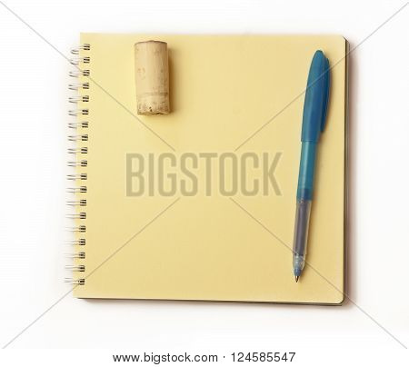 A blue pen and a wine cork on a yellow page of a spiral notebook a photo of a notepad for tasting notes or a template for a wine-related announcement